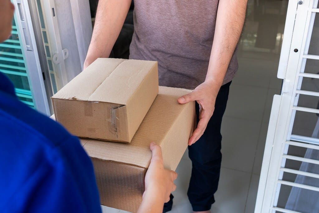 courier delivery man checking or holding cardboard parcel package to deliver to client for accepting a delivery of boxes