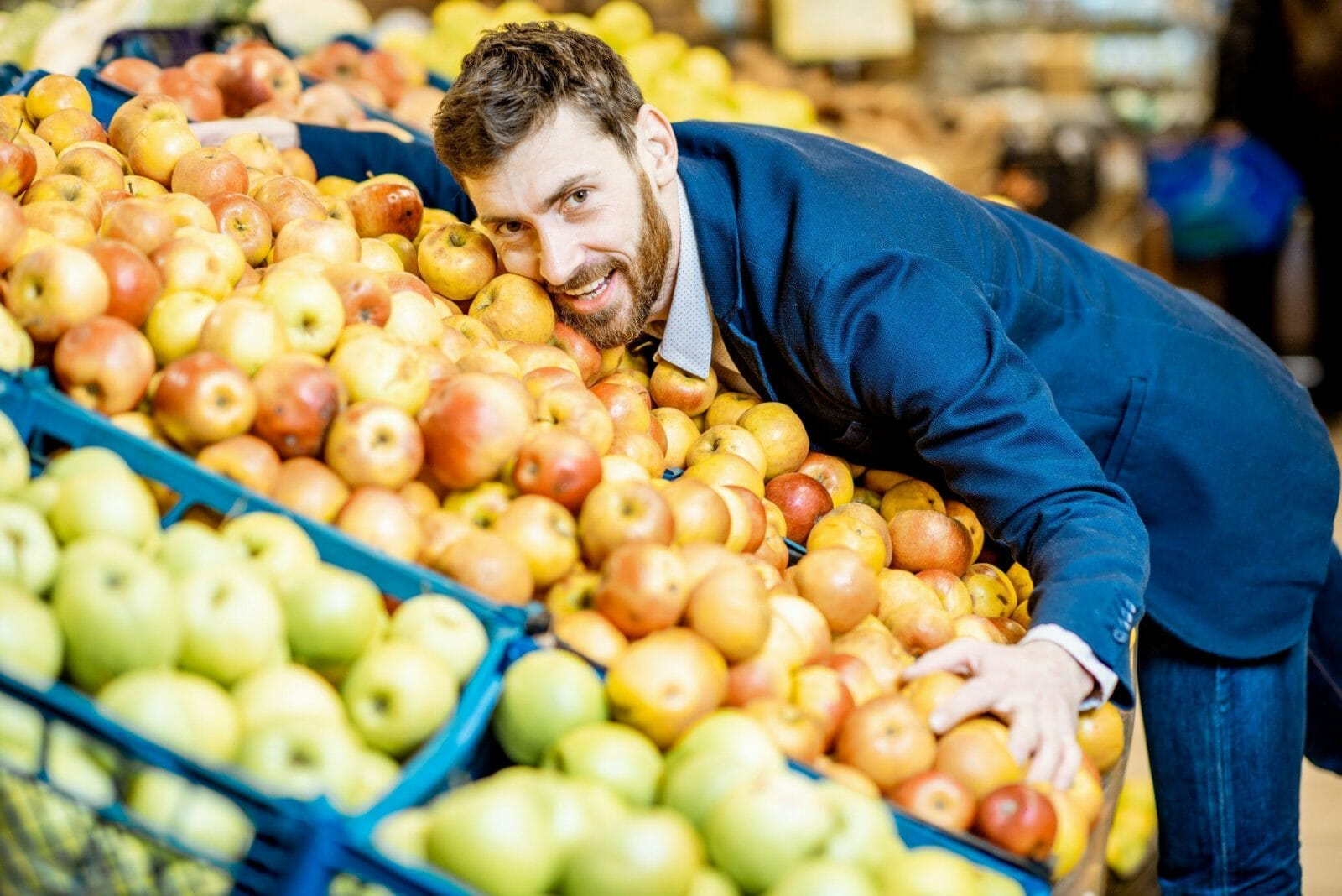 Funny portrait of a businessman hugging a pile of apples in the supermarket in the department with fruits and vegetables