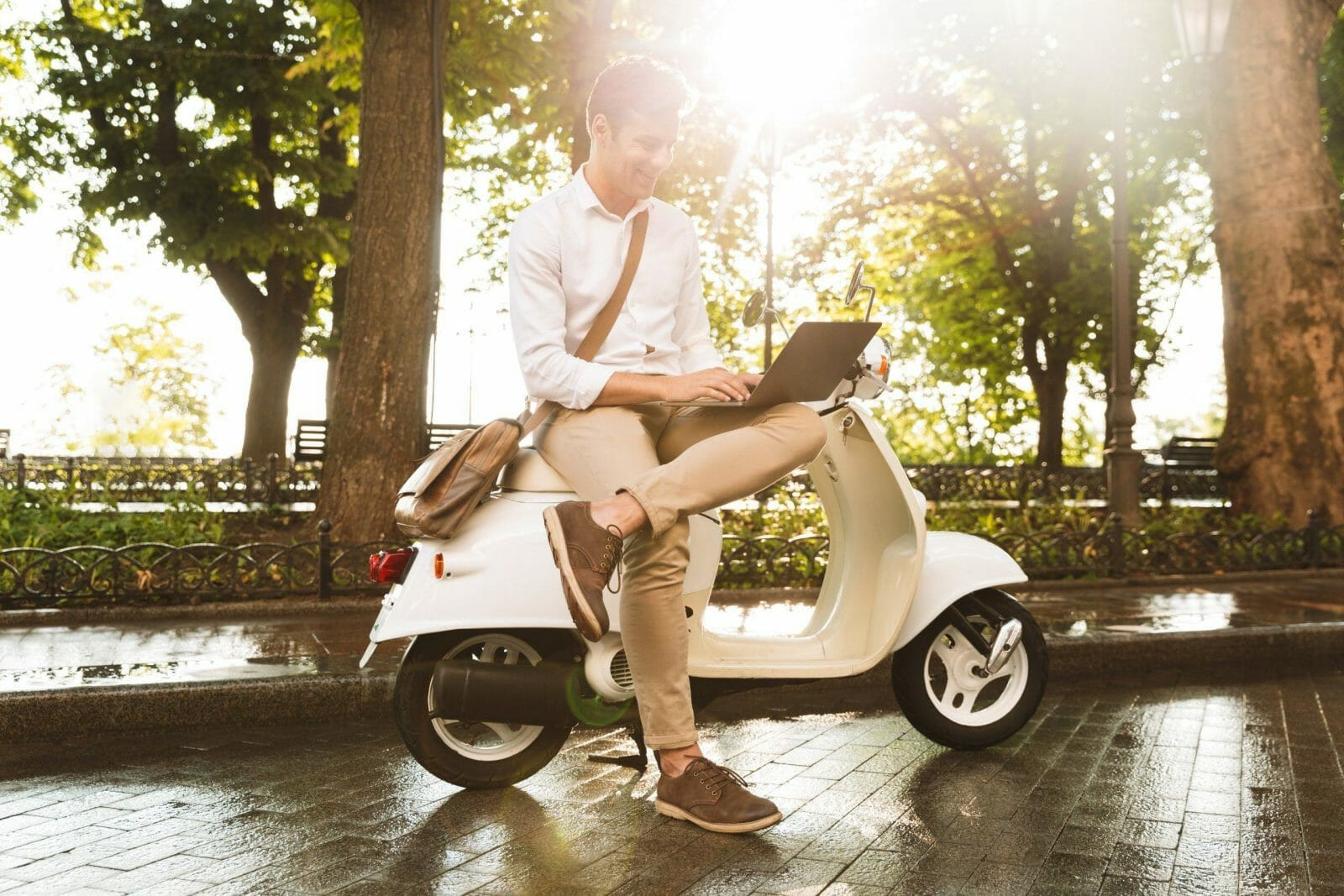 Cheerful young businessman sitting on a motorbike outdoors, working on laptop computer