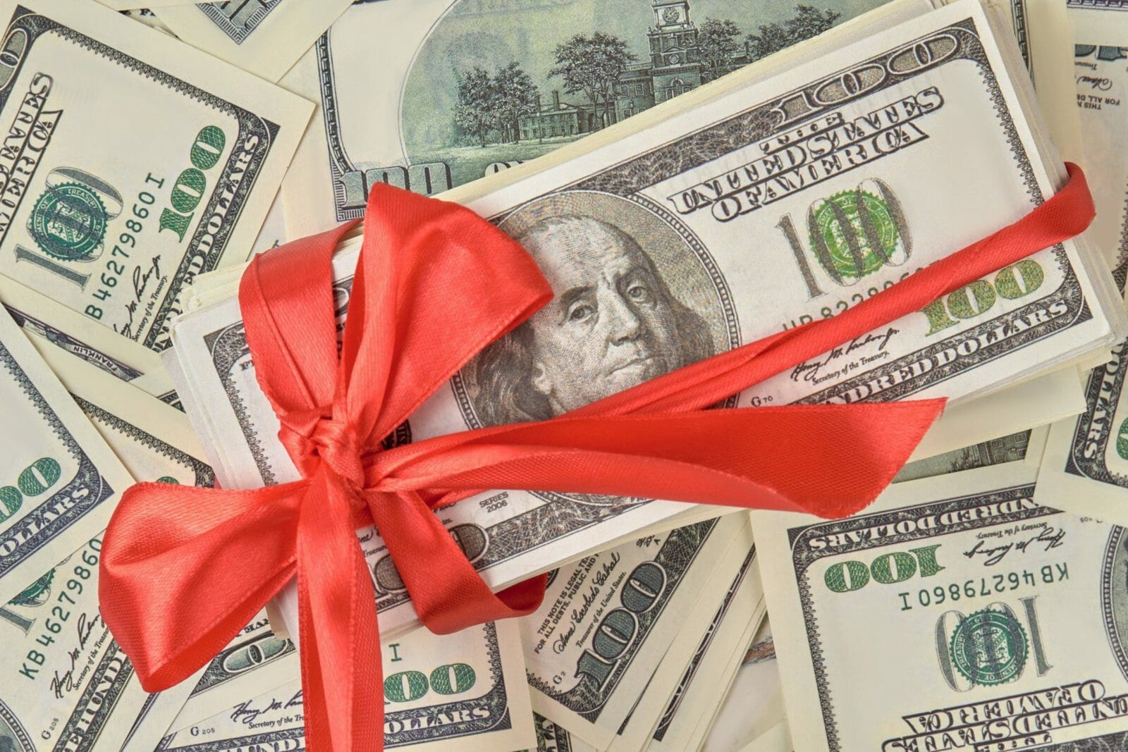Money gift concept. Gift of money with red ribbon on money american hundred dollar bills.