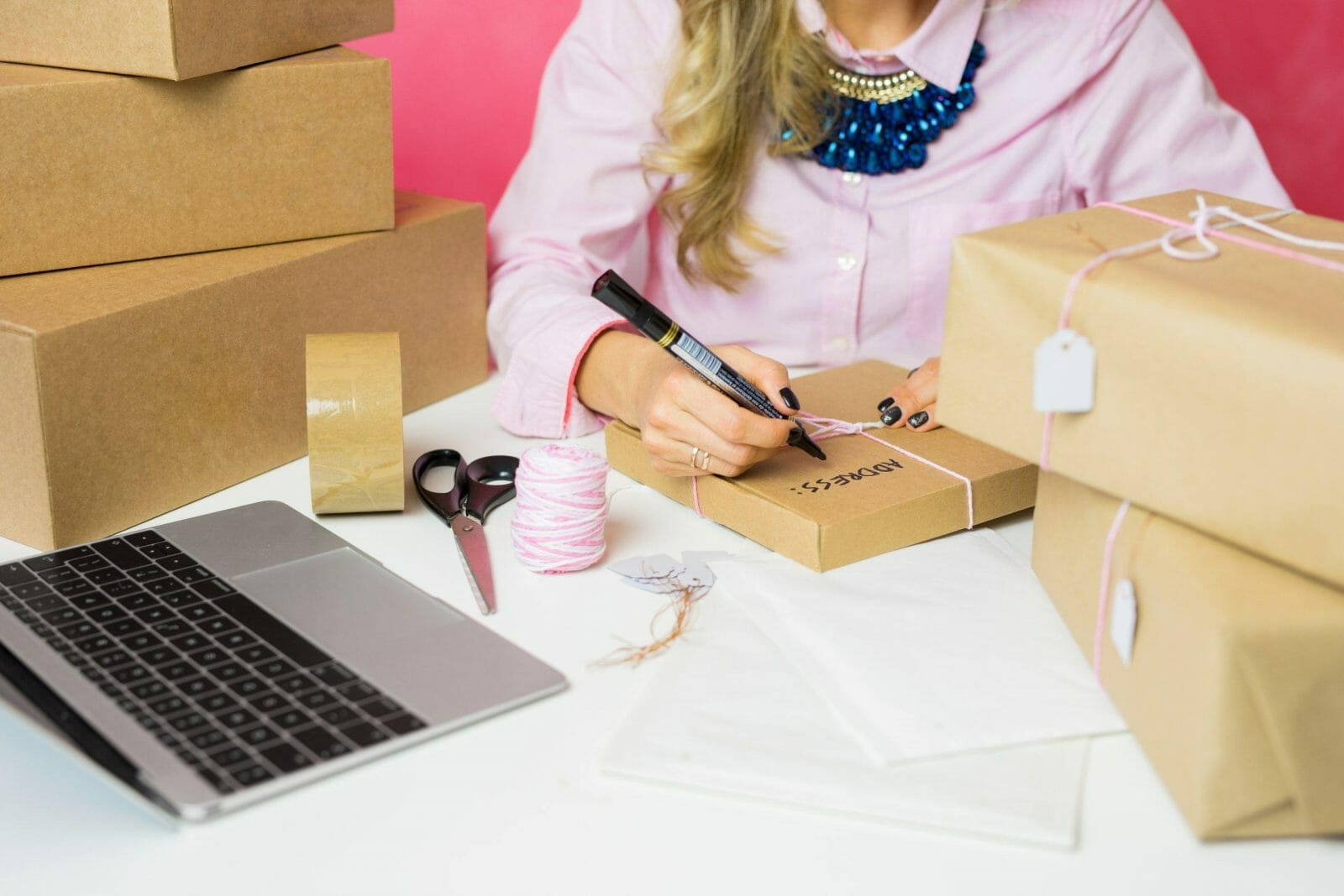 Young woman selling products online and packaging goods for shipping.