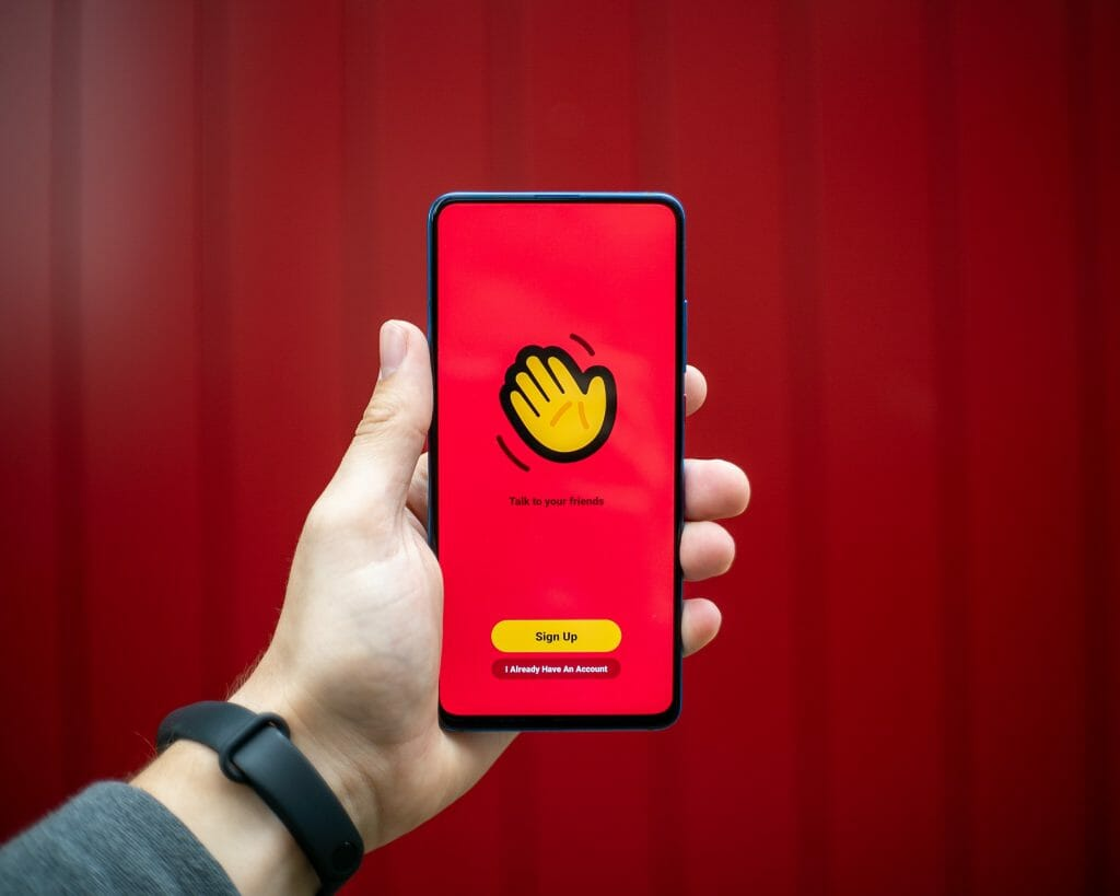 person holding yellow and black iphone case